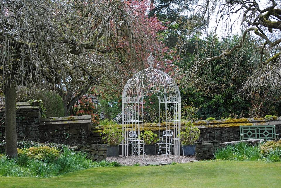 jaula grande con sillas dentro en jardín