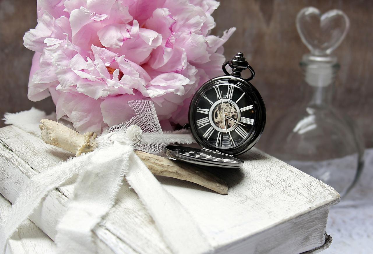 un libro y encima un reloj con flores rosas
